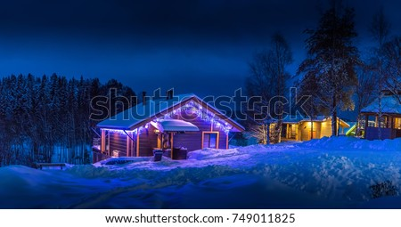 Stock Photo A country house decorated with a light garland. Cottage in the wild in winter.