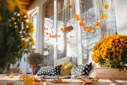 A country house with large panoramic windows decorated for Halloween. Spacious wooden playground with flowers, pillows and garlands