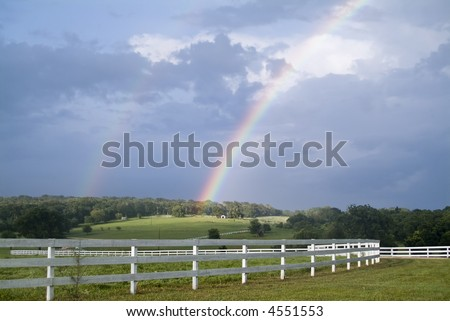 A country landscape with two rainbows accenting the sky during a break in the weather.