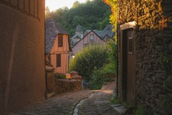 A country lane in the quaint and charming medieval French village of Conques, Aveyron, a popular summer tourist destination in the Occitanie region of France.