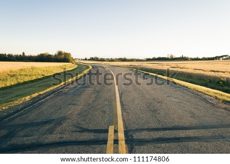 A country road at sunset surrounded by fields