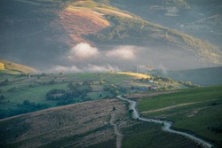 A country road rides up the hills on a misty summer morning in the rural countryside of Lugo