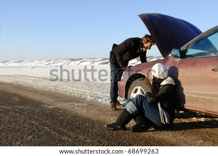 A couple are stranded at side of highway with a car breakdown in winter.