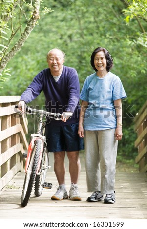 A couple asian mature talking while walking and exercising at a park