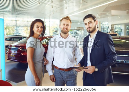 A couple buys a new car. A man and a car salesman make a handshake