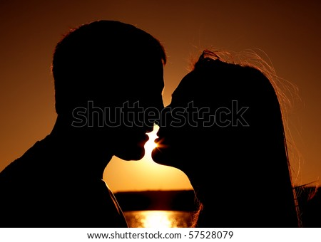 A couple by the water with a deep red orange sky getting ready to kiss each other.