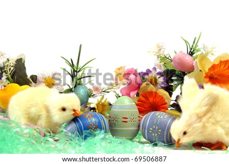 A couple chicks with some easter eggs and flowers.
