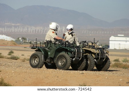 A couple cops patrol a desert airport on their ATV's.