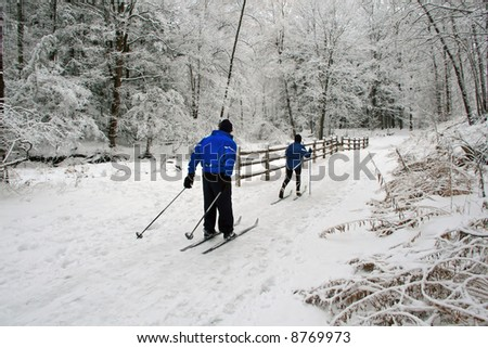 A couple cross-country ski a wintertime trail amid a recent beautiful snowfall.