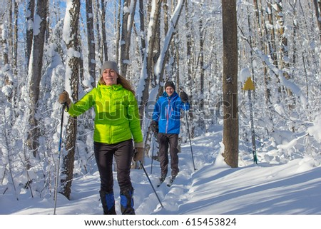 A couple cross country skis in fresh snow in canada #615453824