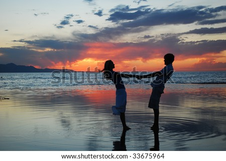 A couple dancing at a lake during a sunset.