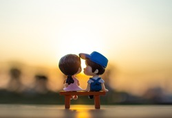A couple dolls sitting on a bench watching the evening sunset Valentine day concept