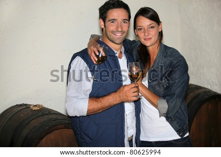 a couple drinking wine in a wine producer's cellar