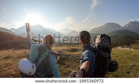 A couple enjoying an early morning in Italian Dolomites. The valley below is shrouded in morning haze. In the back there are high mountain chains. Sun slowly rising above the peaks. Golden hour. Foto stock ©