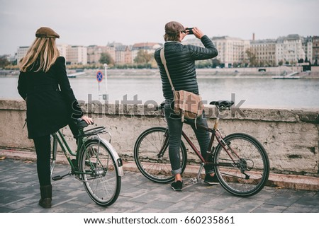 A couple enjoys bicycle ride on the Danube river embankment in Budapest, Hungary.  Toned picture