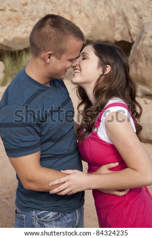 A couple getting ready to kiss each other on the beach and rocks.