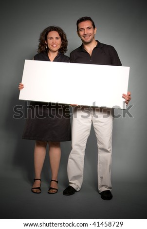 A couple holding a blank sing board, ideal for inserting your own message