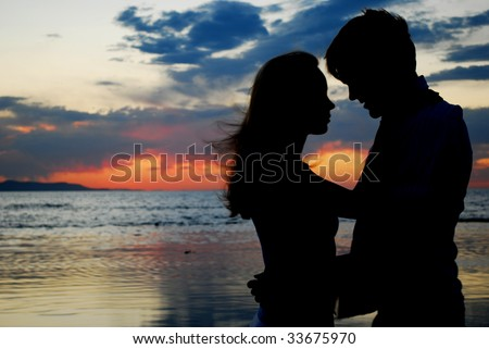 A couple holding each other during a brilliant sunset