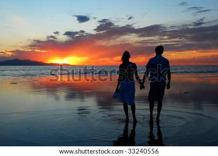 A couple holding hands during an amazing sunset