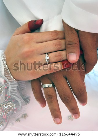 A couple holding hands with rings showing