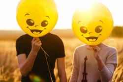 A couple holding yellow balloon with smile face emotion instead of head. Positive Thinking concepts. hiding some bad feeling just keep smiling