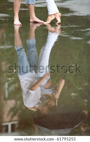 A couple hugging under umbrella reflected in a puddle
