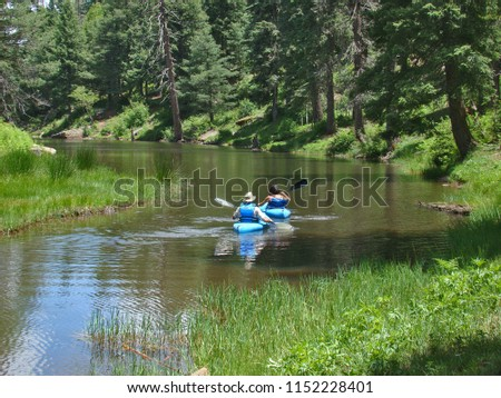 A couple in blue canoes paddling on Woods Canyon Lake on the Mogollon Rim east of Payson in Arizona.