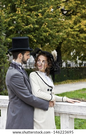 A couple in love, dressed in the style in the end of the 19th century, in the park.