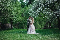 a couple in love embraces in a blooming garden