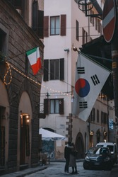 A couple in love in the streets of Florence with some flags around them