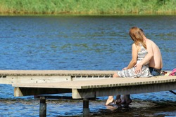 A couple in love is resting on a pontoon by the lake. Married couple on vacation by the pond