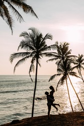 A couple in love meets a sunset on the sea among the palm trees. Man and woman at sunset. Honeymoon on the Islands. Honeymoon trip. Happy loving couple. Silhouette lovers. Wedding travel