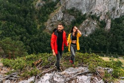 A couple in love on a rock admires the beautiful views. A man and a woman on a rock. A couple in love travels. A walk in the mountains. Couple traveling through the mountains. Hiking. Copy space