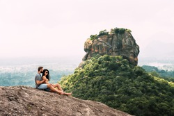 A couple in love on a rock admires the beautiful views. Boy and girl on the rock. A couple in love travels. Couple in Sri Lanka. Honeymoon in Asia. Man and woman in Sigiriya. Couple in the mountains
