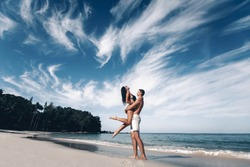 A couple in love on a tropical beach against the blue sea and sky with clouds. A man lifts his woman in his arms