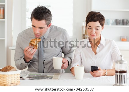 A couple is having breakfast before work