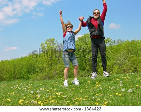 A couple jumps for joy in a meadow