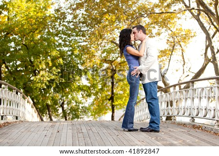 A couple kissing while walking in the park