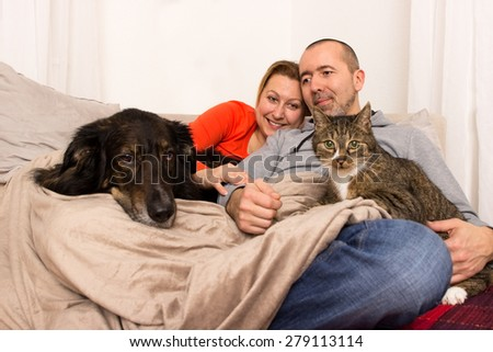 A couple lying with her dog and her cat on the sofa