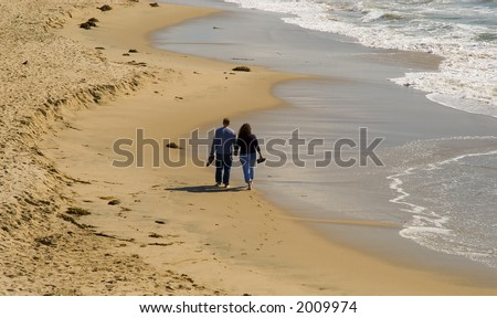 a couple,man and woman,walk holding hands on the beach at the waters edge.