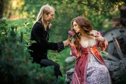 A couple of a beautiful young people posing in vintage medieval dresses on a nature background. Love story.