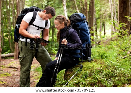 A couple of backpackers looking at a map in the forest