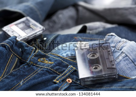 A couple of blank audio cassettes, one of them still in its box, laid on the background of various pairs of jeans pants.