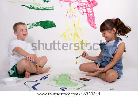 A couple of children have fun paiting pictures.