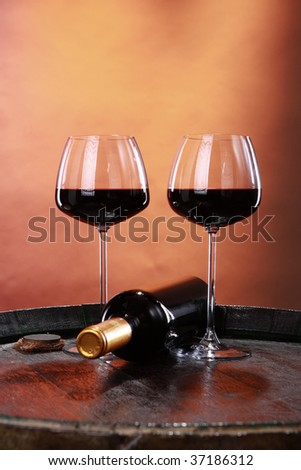 A couple of elegant glasses of red wine on an old barrel top