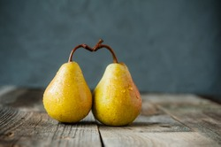A couple of Fresh ripe organic yellow pears form the shape of the heart on rustic wooden table on the dark gray stone background. Relations, love. care concept. Selective focus. Space for text