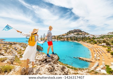A couple of friends in love with the Greek flag admire the grandiose view of the sea Bay and the beach near the ancient city of Lindos. Honeymoon and travel