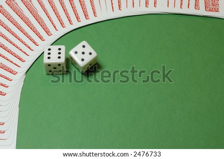 A couple of gambling dices framed  by playing cards on a casino table background