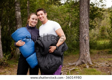 A couple of happy campers standing with sleeping bags