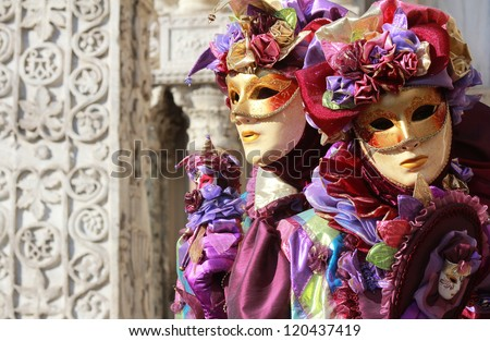 A couple of purple jokers . Marble column as background . Venice carnival 2012